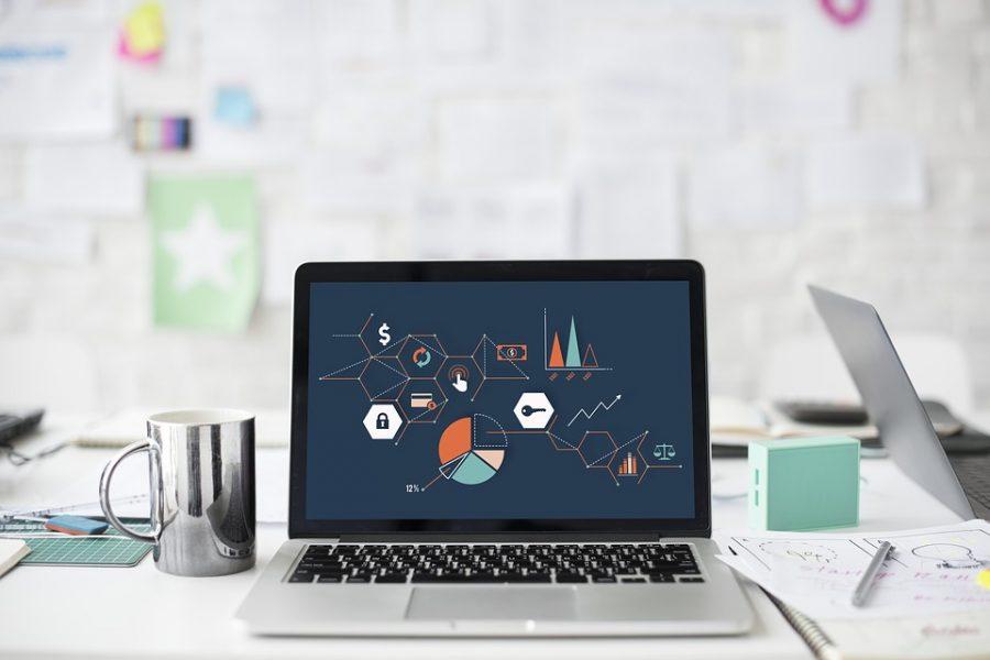 ordinateur portable avec graphiques à l'écran posé sur un bureau avec fournitures de bureau