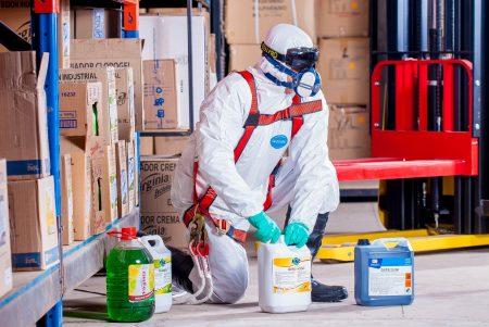 Personnes en combinaison de protection qui manipule des produits chimiques